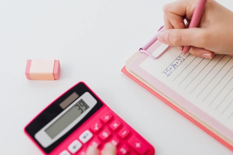 Henkilö laskee lainan hintatietoja laskimella vihkoon