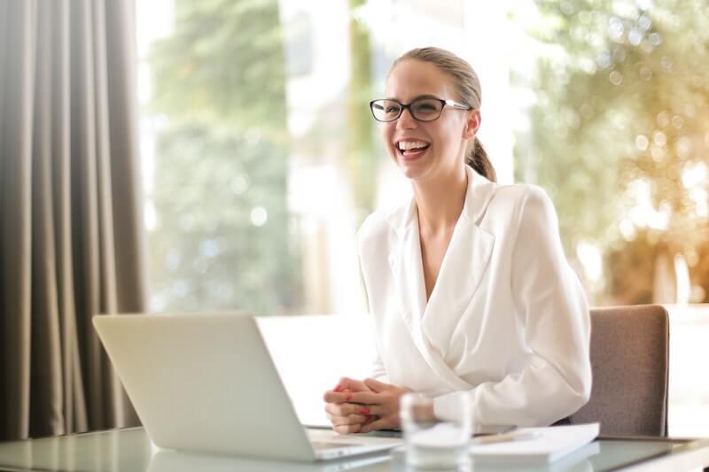 Etf ja indeksirahastoihin sijoittanut nainen hymyilee tietokoneen ääressä
